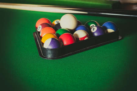 cue sticks: Billiard balls and cue stick on green table. Pool game Stock Photo