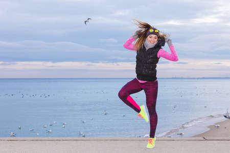 outdoor sport: Sports and activities. Slim fit fitness woman outdoor. Athlete happy smiling girl training wearing warm sporty clothes outside in cold weather.