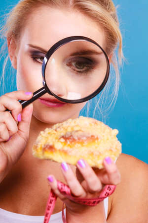 food inspection: Woman measuring tape around hand checking examine sweet roll bun with magnifying glass. Female with fattening junk food. Bad unhealthy eating nutrition concept.