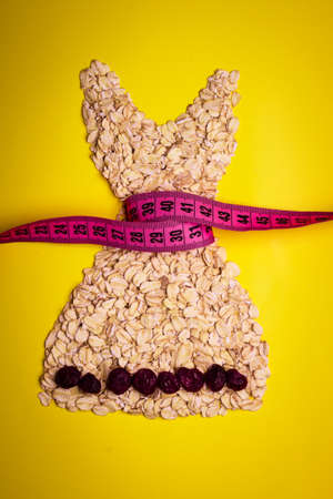 dress form: Dieting healthy eating slim down concept. Female dress shape made from oatmeal dried fruit with measuring tape around thin waist on yellow Stock Photo