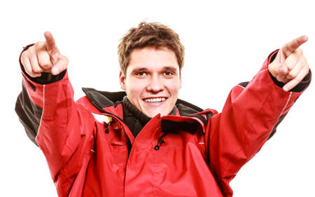 outdoorsman: Male outdoorsman making gestures. Young man with weatherproof gear. Communication outdoor adventure danger concept.