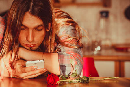 unloved: Disappointment and depression. Unrequited love concept. Young worried disappointed man with single red rose and smartphone mobile phone waiting for his girlfriend.