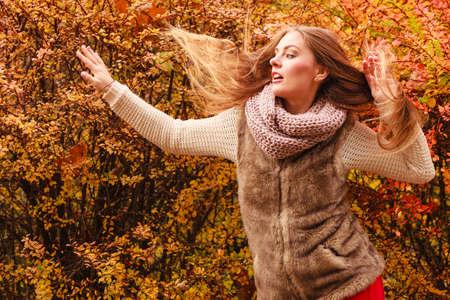 mystery woman: Beautiful autumn season. Fashionable mystery woman posing against colorful autumnal leaves outdoor in park