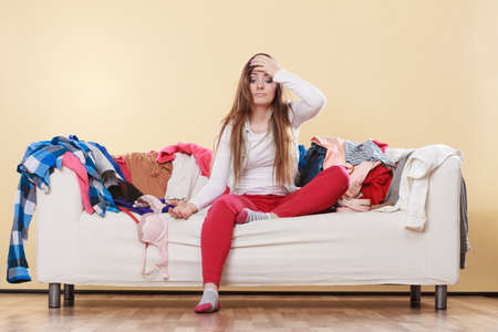Desperate helpless woman sitting on sofa couch in messy living room with hand on head. Young girl surrounded by many stack of clothes. Disorder and mess at home.