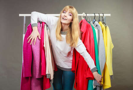 bought: Pretty happy woman between clothing from wardrobe. Young undecided shopper girl having fun and bought new clothes. Shopaholic concept.