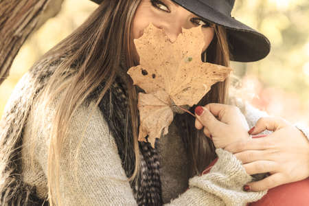 Seasonal specific. Gorgeous lovely young girl holding gold brown leaf. Beauty trendy woman spending time in autumnal park. Stock Photo