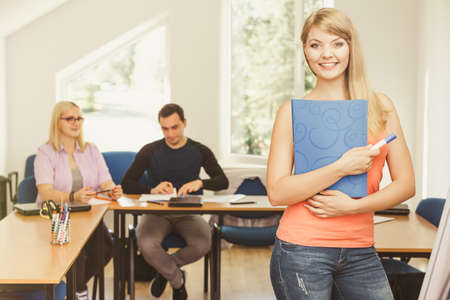 mates: Education, high school, teamwork and people concept - smiling student girl with notebook standing in front of students her group mates in classroom