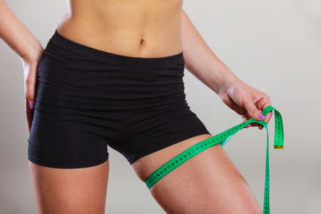 Weight loss, slim body, healthy lifestyle concept. Fit fitness woman in sportswear measuring her thigh with green measure tape