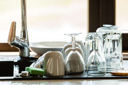 houseware: Washing up. Modern sink and kitchen counter with claen dishwares, window in the background