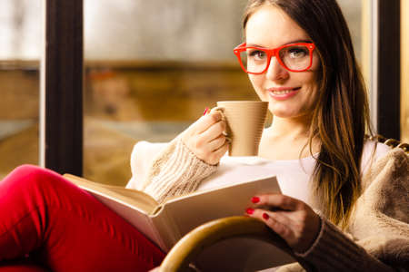 Calm and coziness. Young woman at home sitting comfortable on rocking chair in front of window relaxing in her living room reading book holds coffee mug