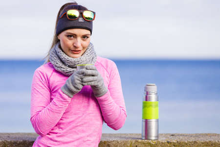 outdoor sport: Woman athlete fit girl wearing warm sporty clothes outdoor in cold weather drinking hot tea from vacuum flask thermos, warming up. Sports, activities, hiking in winter or autumn time Stock Photo