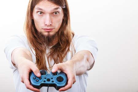 jugando videojuegos: Estilo de vida de los jóvenes. Hombre del estudiante pasar el tiempo jugando juegos de consola de videojuegos. Larga chico de pelo enfoque en el juego. Foto de archivo
