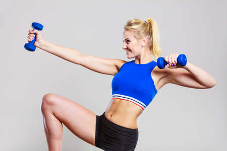 slim women: Sporty woman lifting light dumbbells weights. Fit girl exercising building muscles. Fitness and bodybuilding.