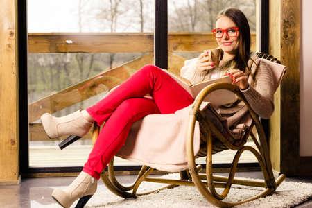 rocker girl: La calma y la comodidad. La mujer joven en su casa sentado cómodo en mecedora delante de la ventana se relaja en su libro de lectura de la sala de estar sostiene la taza de café