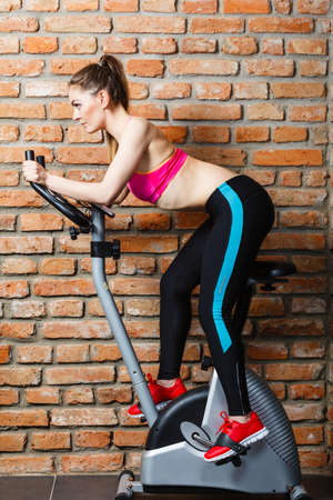 out of body: Active young woman working out, doing sport biking in the gym for fitness. Sporty girl training in club. Slim body weight loss concept. Side view. Stock Photo