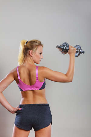 gaining: Strong woman lifting dumbbells weights. Fit girl exercising gaining building muscles. Fitness and bodybuilding, back view Stock Photo