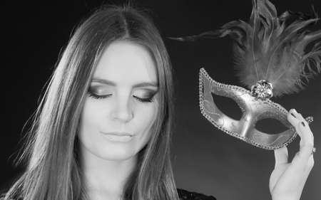 Party time, holidays, people and celebration concept. Woman long hair holding carnival mask close up. Black & white photo