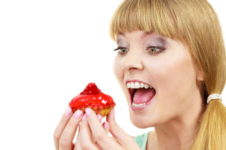 Woman holds cake cupcake in hand taking a huge bite out of dessert, eating unhealthy junk food. Sweetness indulging and fattening concept Stock Photo