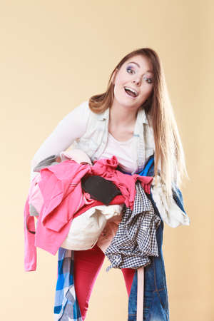 tidying: Young woman carrying stack pile of dirty laundry clothes. Girl cleaning tidying in studio.