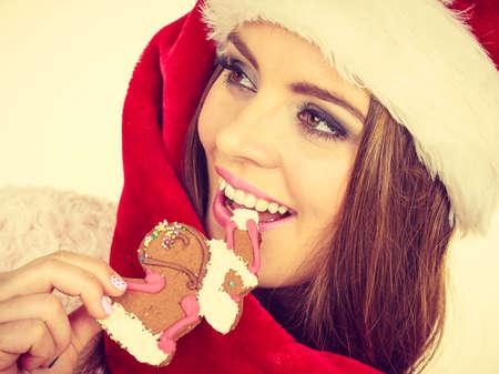 65017703 - Mujer que lleva el sombrero rojo que sostiene la galleta dulce  deliciosa de Navidad del pan de jengibre pequeño Papá Noel. d564dad5780