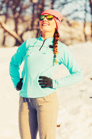 Warm up in winter. Girl exercising in frozen park. Health fitness nature concept.