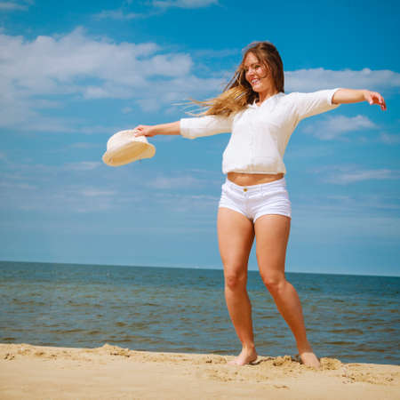 craze: Happiness and craziness. Smiling crazy girl have fun outdoor. Young attractive long haired woman playing on summer beach. Stock Photo