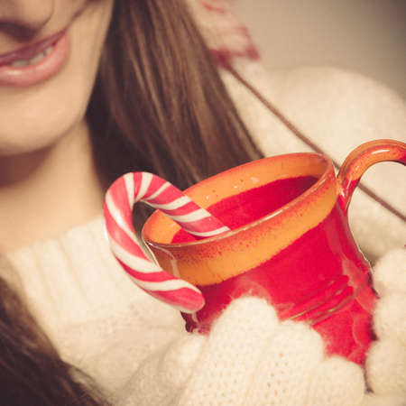Christmas helping giving concept. Close up of woman hands holding red mug with beverage and sweet cane.