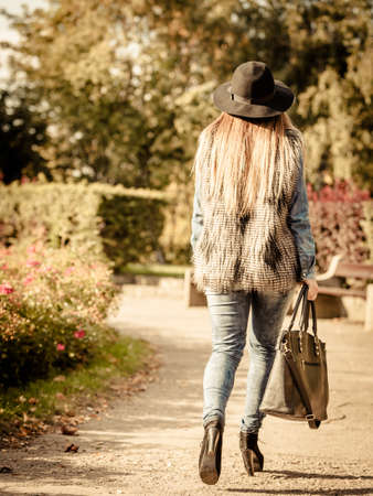 back alley: Female fashion. Back view of attractive long haired model wearing stylish clothes in park. Fashionable young model spending time on air.
