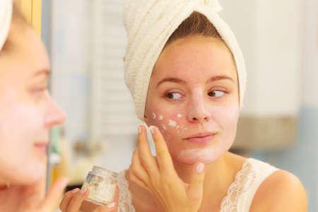 Vrouw van toepassing zijn masker hydraterende crème op gezicht op zoek in de badkamer spiegel. Meisje het verzorgen van haar teint gelaagdheid moisturizer. Skincare spa. Stockfoto - 65018489