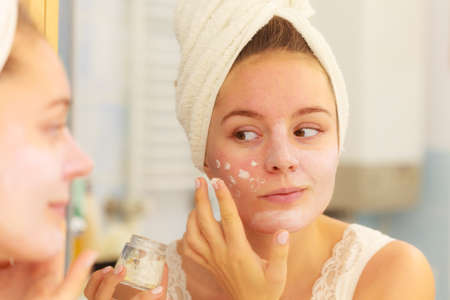 moisturizers: Woman applying mask moisturizing skin cream on face looking in bathroom mirror. Girl taking care of her complexion layering moisturizer. Skincare spa treatment.