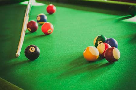 pool game: Billiard balls and cue stick on green table. Pool game Stock Photo