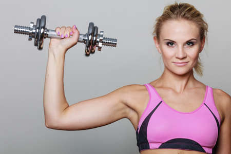 gaining: Strong woman lifting dumbbells weights. Fit girl exercising gaining building muscles. Fitness and bodybuilding. Stock Photo