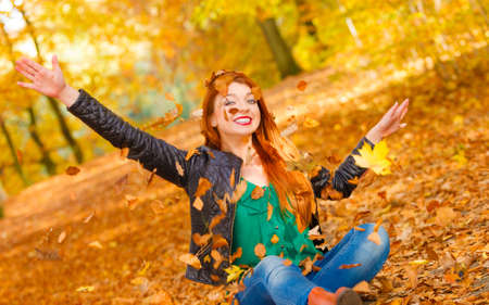 tossing: Nature outdoor playing relax leisure concept. Crazy girl throwing leaves. Euphoric redhead woman tossing around autumnal foliage having time of her life.