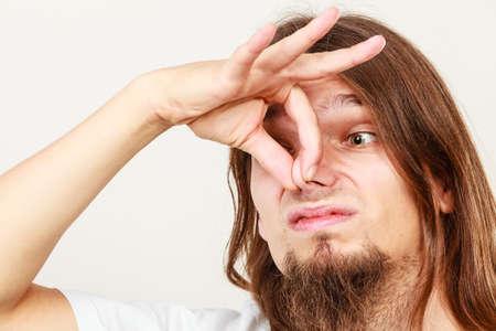 Expresión de muy mal olor. larga gesto sudorosa joven de pelo toma de la mano del hombre. concepto de la sudoración.