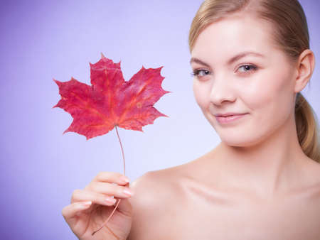 Skincare habits. Portrait of young woman with leaf as symbol of red capillary skin on violet. Face of girl taking care of her dry complexion. Studio shot. Stock Photo