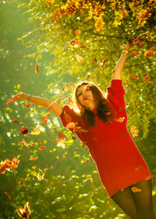 tossing: Woman playing with autumnal leaves. Young girl in park tossing foliage. Nature outdoor relax scenery concept.