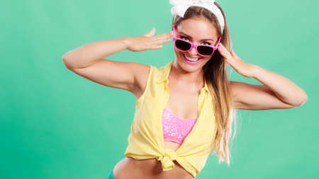 hairband: Portrait of happy smiling pretty pin up girl with hairband bow wearing sunglasses. Attractive gorgeous young retro woman posing in studio on green background.