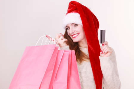 buying time: Christmas time. Young latin woman wearing santa claus hat holding red shopping bags and credit card, buying gifts
