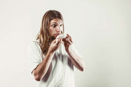 hygienic: Allergy and cold concept. Young long haired sick man with hygienic tissue. Guy blowing nose.