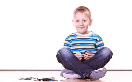 collect: Free time, fun and hobby. Little boy play indoors sit on floor and play collect cards.