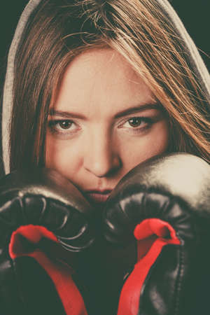 sportsmanship: Fighting boxing and defense. Sportsmanship and strong body. Young woman wear sportswear and boxing gloves cover face look at opponent. Stock Photo