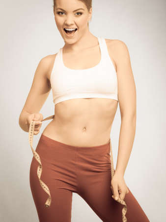 losing control: Time for diet slimming weight loss. Health care and healthy nutrition. Fitness woman fit girl with measure tape, instagram filter