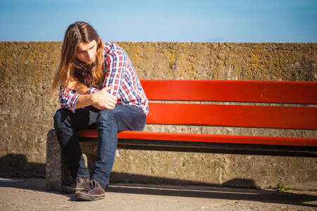 Man long hair alone on bench, lost in thought, is concerned and stressed about events in his life. Unemployment depression concept