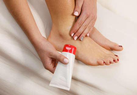 bad skin: Woman fit girl putting ointment cream on bad injured ankle or applying moisturizer cosmetic cream on foot. Health skin care.