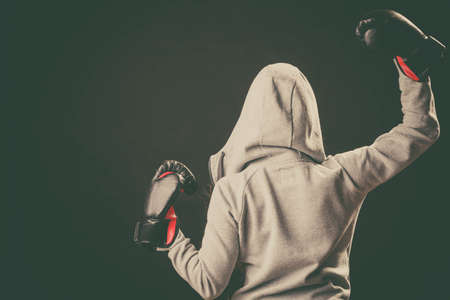 sportsmanship: Sportsmanship and strong body. Win fight with opponent. Young woman wear hoodie victory pose show emotion with arms in air. Girl wear boxing gloves.