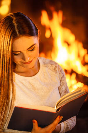 fireplace home: Woman reading book at fireplace. Young girl heating warming up and relaxing. Winter at home.