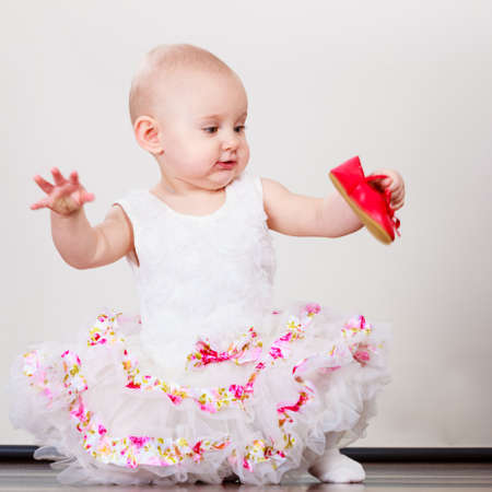 tot: Lovely little child girl in princess fairy dress. Portrait of cute beauty sweet baby ballerina playing wit red shoes. Stock Photo