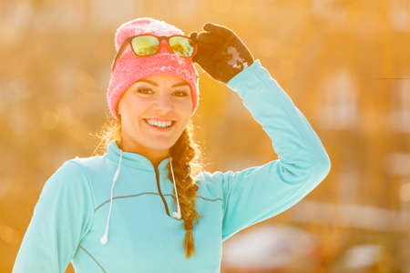 enviroment: Fit girl posing in park. Showing beauty in winter enviroment. Health nature fitness fashion concept.