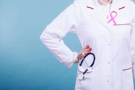 Women fight for health. Breast cancer tumor concept. Pink ribbon on white medical apron uniform and blue stethoscope in pocket.