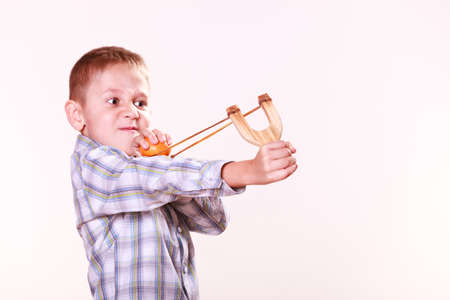 mandarine: Nature and free time prankster little boy. Child have fun with  wooden sling shot and fruit aim mandarine.